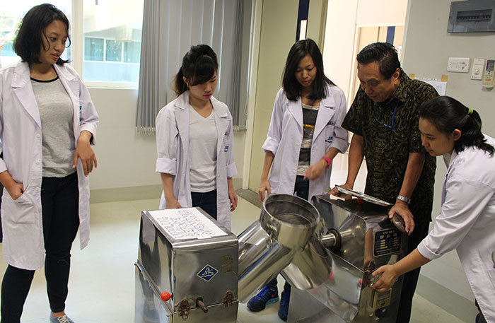 Praktik industri obat di lab jurusan Pharmaceutical Engineering. Mahasiswa sedang mencampur bahan obat dengan blender khusus.