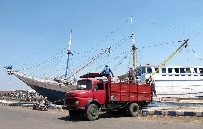 Pelabuhan tradisional di Pasuruan dengan kapal-kapal kayu dan truk tua.